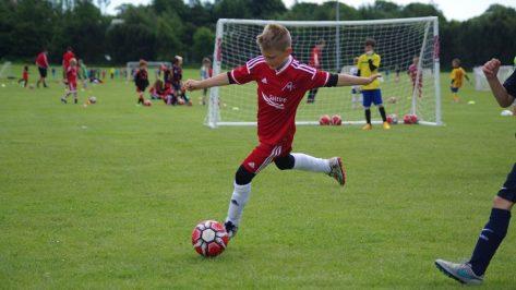 youngboykickingfootball