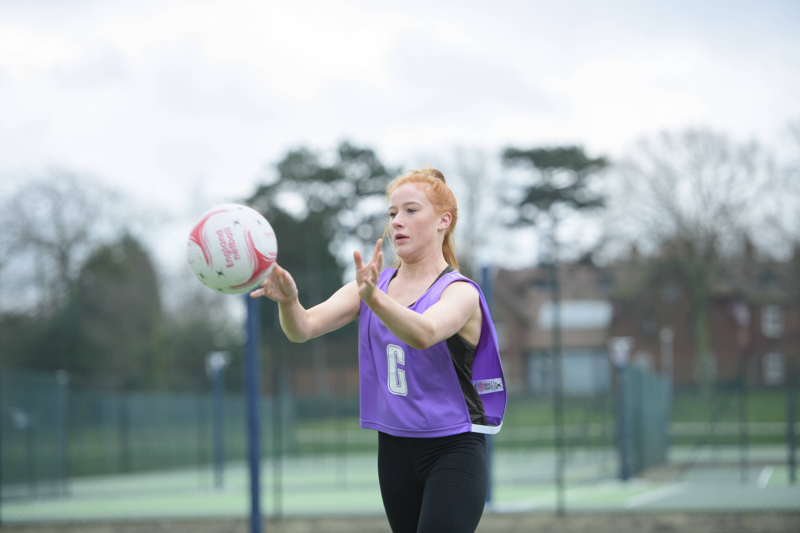 Female playing netball outdoors