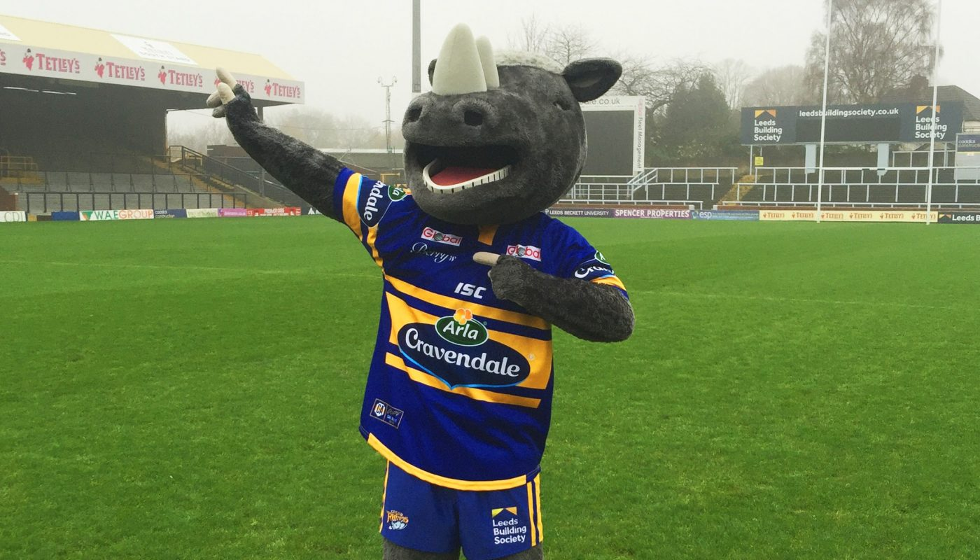 The image is of the leeds rhinos mascot Ronnie the rhino. He is stood up with his right arm bent in and his left arm stretched out.